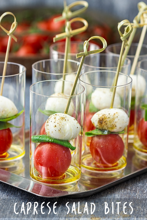 A fancy looking appetizer that is ready in minutes! Caprese salad bites are easy to make and crowds love them. These refreshing bites are drizzled with olive oil, secured with a stick and served in a mini glass. #appetizeraddiction #partyfood #appetizers