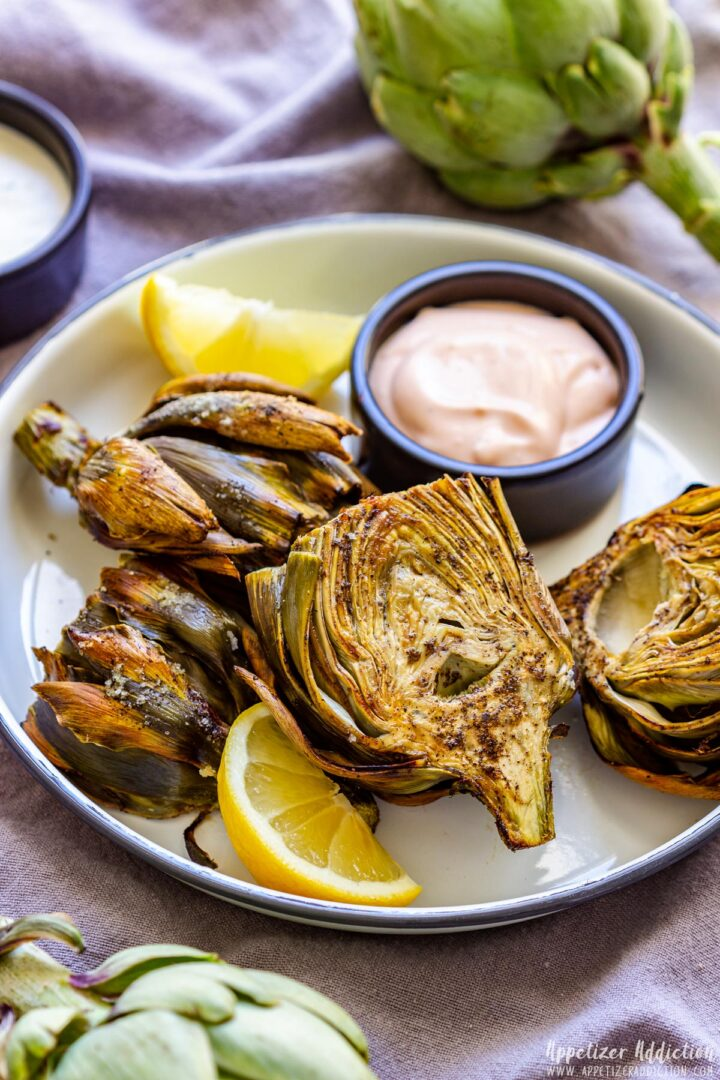 Air Fryer Artichokes on a white plate with sauce and lemon wedge