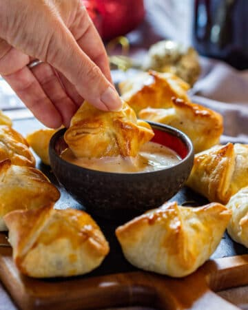 Dipping beef wellington bites to the sauce