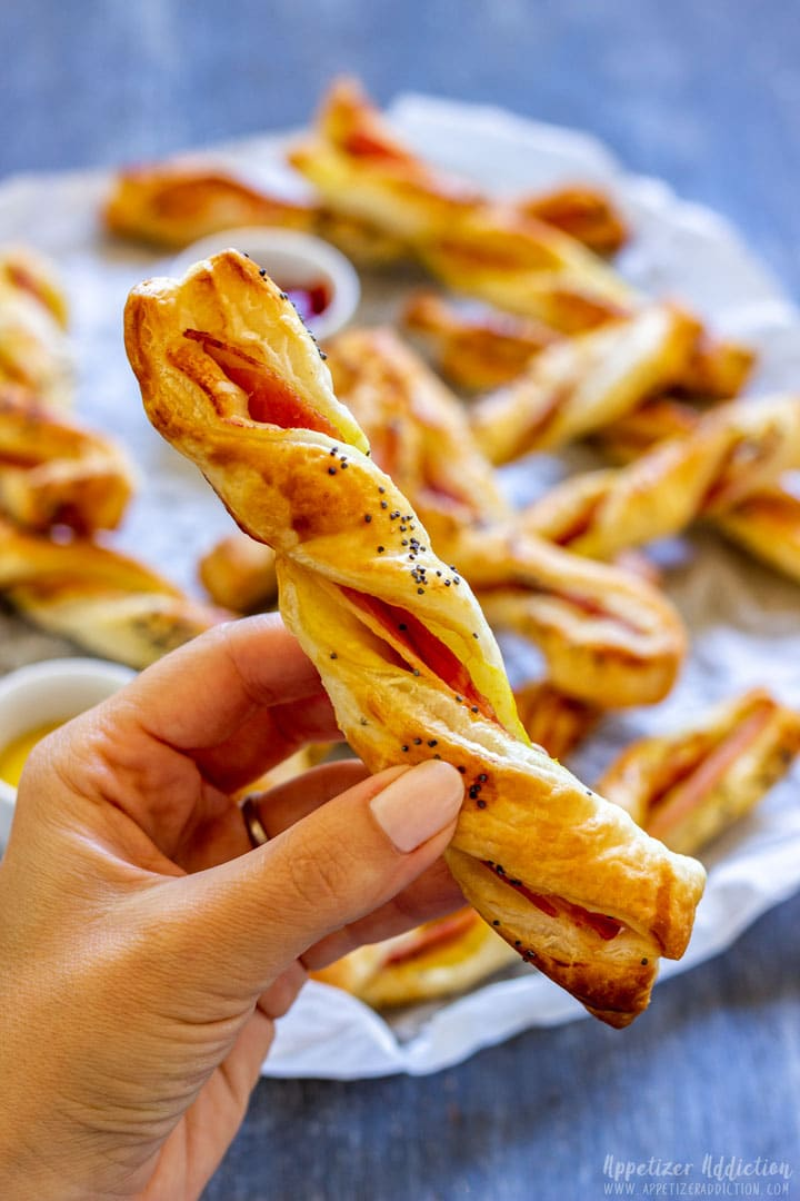 Holding bacon puff pastry twists, ready to take a bite
