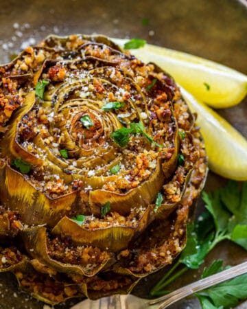 Stuffed artichoke on the plate with slices of lemon