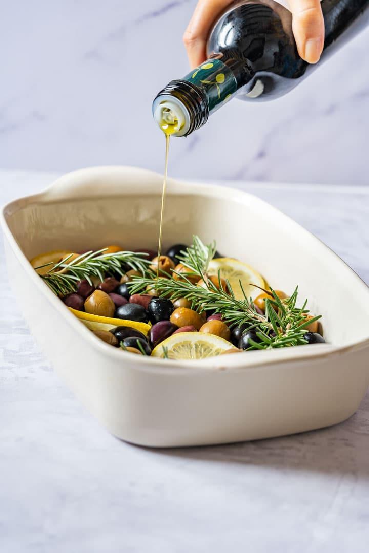 Pouring olive oil over olives