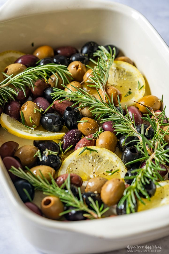 Olives, lemon slices and rosemary ready to be baked