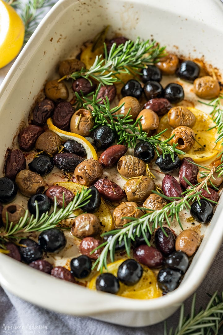 Baked olives with lemon slices and rosemary
